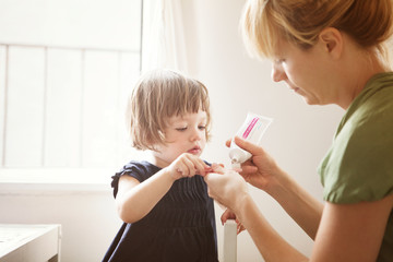 Mother applying toothpaste on daughter's (2-5 months) toothbrush
