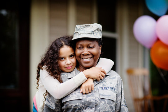 Portrait of daughter hugging her soldier mother outdoors