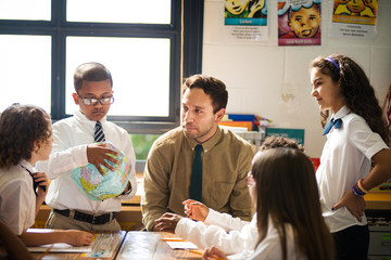 Male teacher helping group of students (6-7, 8-9) with project