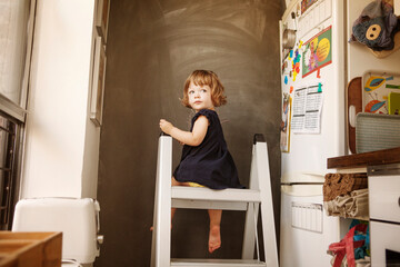 Girl sitting on ladder in kitchen