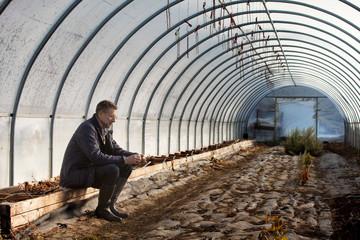 Mature man sitting in greenhouse
