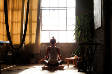 Rear view of woman meditating in living room