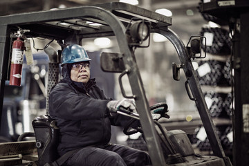 Portrait of man driving forklift in warehouse