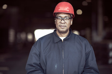 Portrait of mature worker standing in factory