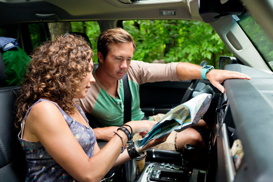 Man and woman in car checking map