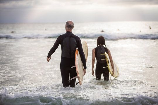 Rear view of couple with surfboards walking in sea