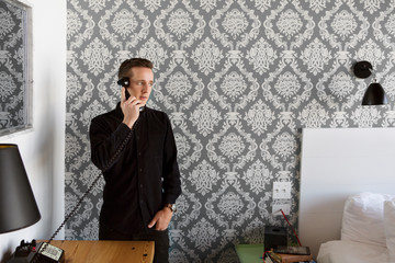 Man talking on telephone in bedroom