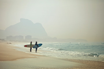 Couple with surfboards standing on beach