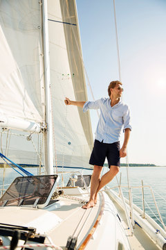 Man leaning off sails of private yacht