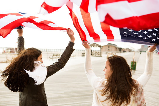 Young woman and teenage girl waving American flags