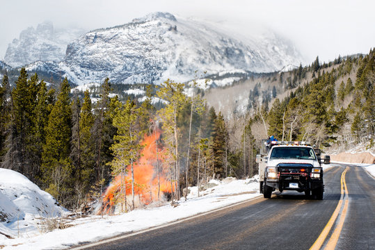 Truck driving by fire in mountains