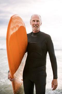 Portrait of senior surfer standing on beach