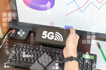 Businessman's hand holds smart phone with 5g icon on display on workplace's office background. 5g wireless mobile technology.