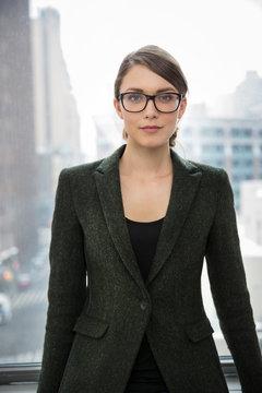 Portrait of businesswoman standing by window