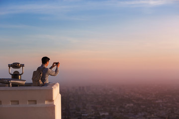 Man taking picture of city with smartphone from observation point