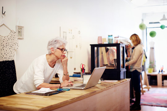 Senior woman working on laptop in boutique