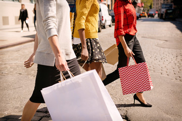 Low section of friends with shopping bags crossing street