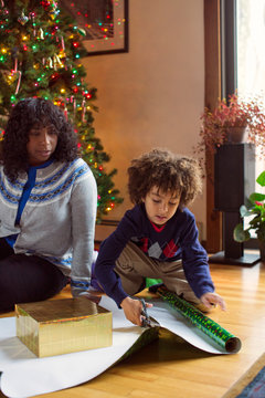 Boy (6-7) helping woman with wrapping christmas presents