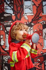Portrait of boy in fire fighter costume (4-5)