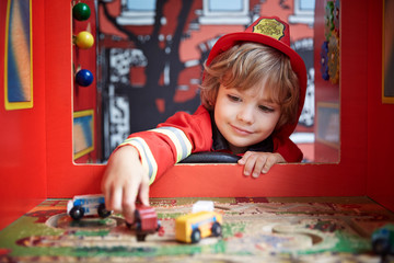 Boy in firefighter costume playing with toy car