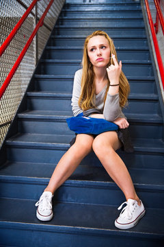 Teenage girl stretching bubble gum on stairs