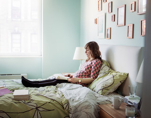 Side view of pregnant woman reading book on bed