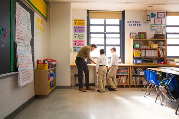 Male teacher and two schoolboys (8-9) standing by windowsill in classroom