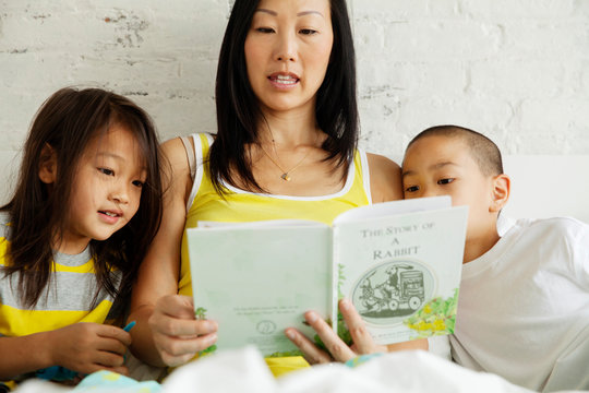 Mother and children reading book on bed