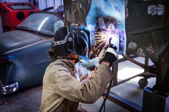 Side view of mechanic welding car body part in workshop