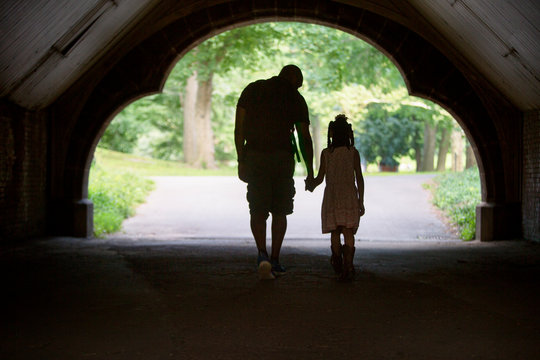 Silhouette of man walking in tunnel in park with daughter (6-7) holding hands
