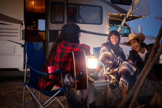 Smiling friends sitting by motorhome at dusk