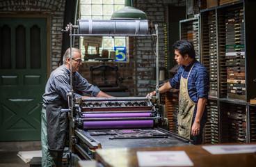 Craftsmen working over printing press in workshop