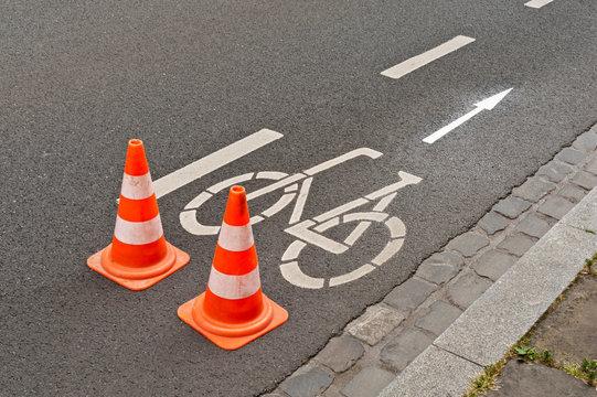 Zwei Pilonen stehen auf der Strasse bei Fahrbahnmarkierungsarbeiten für einen Radweg