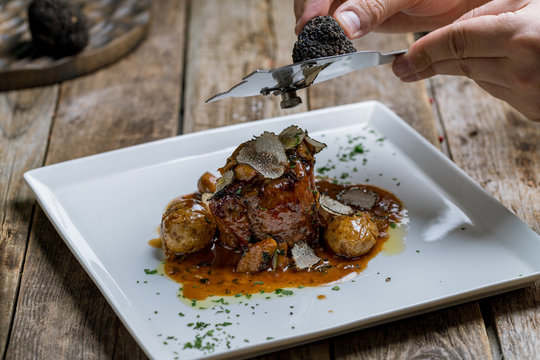 filet Mignon with truffle on white plate on wooden background