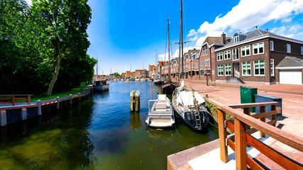 Sailing ships and dutch buildings by the Hoofdtooren in Hoorn, Netherlands by the Hoofdtooren in Hoorn, Netherlands