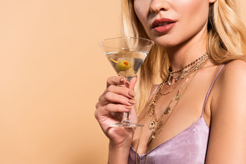 cropped view of elegant blonde woman in violet satin dress and necklace holding cocktail isolated on beige Wall mural