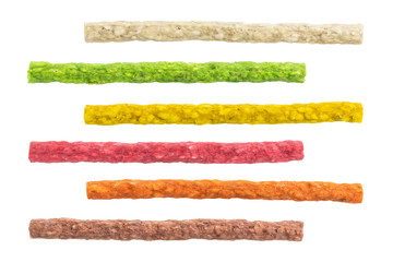 set of colorful dyed rawhide sticks for dog treat isolated on white background