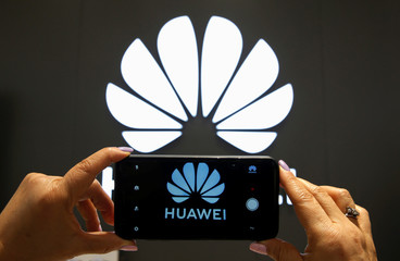 A Huawei logo is seen on a cell phone screen in their store at Vina del Mar