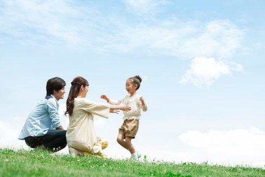 草原で遊ぶ家族3人