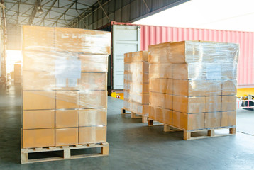 Large shipments pallet goods waiting for load into container truck at warehouse dock. Road freight cargo shipment by truck. Logistics and transportation