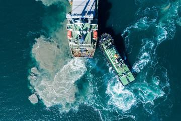 共に海を走る小型船と大型船 空撮