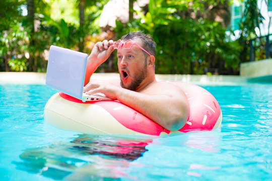 surprised Fat funny man in pink inflatable circle in pink glasses works on a laptop in a swimming pool