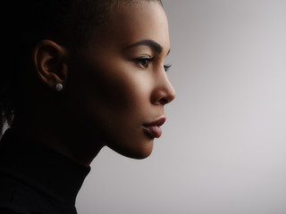 Closeup fashionable portrait of a metis young woman with perfect smooth glowing mulatto skin, full lips, collected hair and long neck. Studio photo of an african american female model face, profile