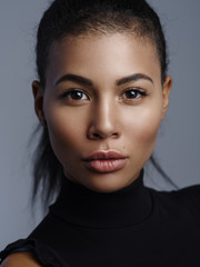 Fototapete - Closeup fashionable portrait of a beautiful metis young woman with perfect smooth glowing mulatto skin, full lips and collected hair. Studio shoot of an african american female model with nude makeup