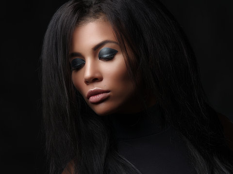 Closeup fashionable portrait of a beautiful mulatto young woman with close eyes, full lips and black lush loose hair. Studio shoot of african american female model with the bright makeup on her face