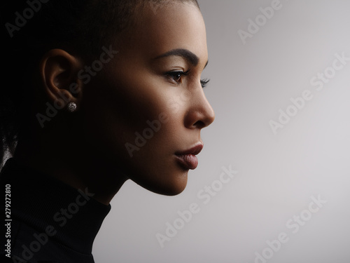 Fototapete Closeup fashionable portrait of a metis young woman with perfect smooth glowing mulatto skin, full lips, collected hair and long neck. Studio photo of an african american female model face, profile