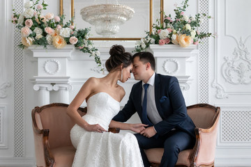 bride and groom communicate sitting in classic chairs against white fireplace with floral arrangements. Newlyweds talk quietly sitting opposite each other.