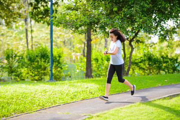 In de dag Ontspanning Young asian woman running in a city park and looks at the smart watch