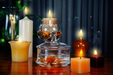 The purified water in the glass jar is charged with the energy of carnelian. The process of the making gem elixir is in progress, surrounded by lit candles on a wooden table.