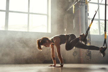 TRX Training. Young athletic woman in sports clothing training legs with trx fitness straps in the...